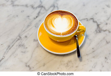 Cup of coffee with foam in heart shape on marble table
