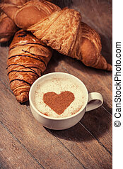 Cup of coffee with french croissant