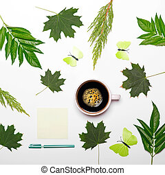 Cup of coffee with green leaves butterfly book and pen on white background - Flat lay