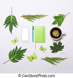 Cup of coffee with green leaves butterfly book pen and cell phone on white background - Flat lay