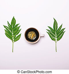 Cup of coffee with green leaves on white background - Flat lay