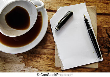 Cup of coffee with grunge notepad and pen on wooden background