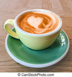Cup of coffee with heart pattern foam in a yellow cup on rustic wooden table background, top view