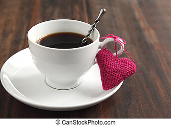 Cup of coffee with knitted heart
