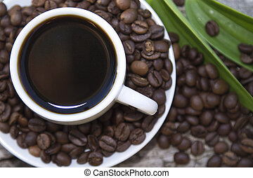 cup of coffee with leaf and beans