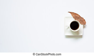 Cup of coffee with leaves on white background. top view