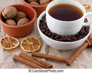 Cup of coffee with lemon, beans and cinnamon on old paper