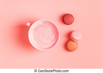 Cup of coffee with macaroons on pastel background.