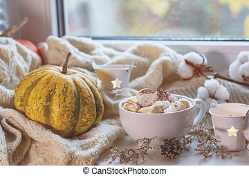 Cup of coffee with marshmallow on windowsill, cozy home concept