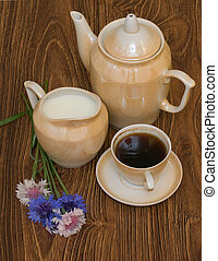 cup of coffee with milk, coffee pot and cornflowers on a wooden table