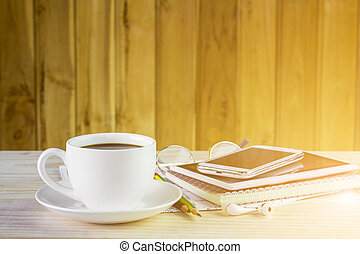 Cup of coffee with note book on wooden table background
