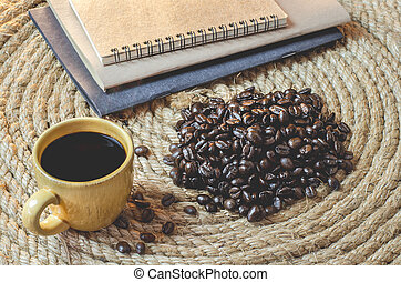 Cup of coffee with  notebook on a jute rope.