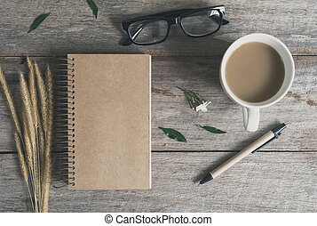 Cup of coffee with notebook on wooden table