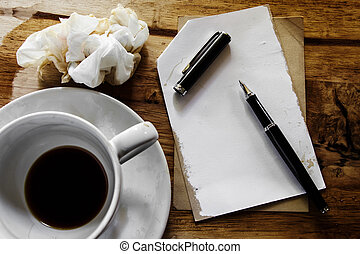Cup of coffee with notepad, pen and crumpled paper on wooden background