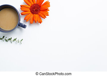 Cup of coffee with orange gerbera daisy flower and eucalyptus leaf on white background. flat lay, top view, copy space