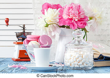 cup of coffee with peonies and an open book on a wooden background.