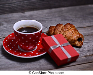 Cup of coffee with present and croissant on wooden