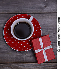 Cup of coffee with present on wooden background