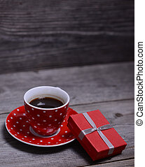 Cup of coffee with present on wooden