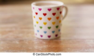 cup of coffee with rainbow colored heart pattern -...