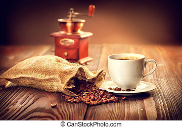 Cup of coffee with sack full of roasted coffee beans and coffee mill on wooden table