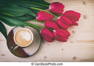 cup of coffee with spring flowers red tulips on wooden table