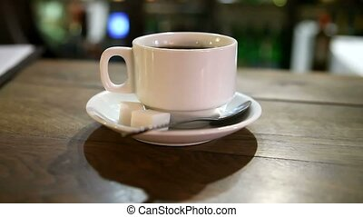 cup of coffee with sugar is at the bar in a cafe