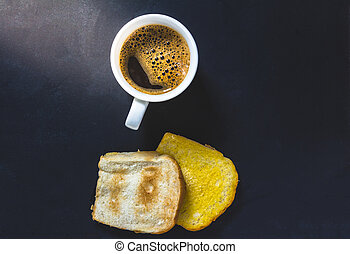 Cup of coffee with toast on black background