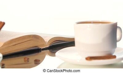 Cup of coffee with turning pages book on white background