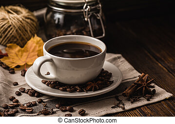Cup of coffee with various spices, beans, leaves