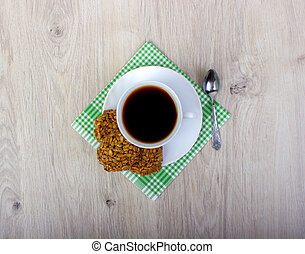 Cup of coffee wiyh pile of various shortbread and oat cookies with cereals on wooden background.