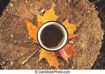 Cup of coffee, yellow maple and oak leaves on the wooden board. Bright autumn background. Sunlight, copy space, top view.