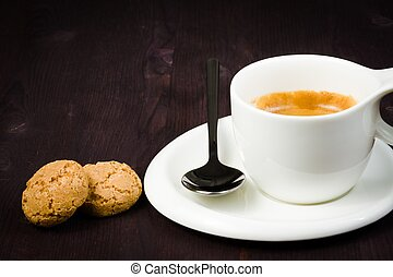 cup of espresso coffee and biscuit near spoon