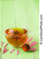 Cup of echinacea tea on green wooden table with copy space for your text