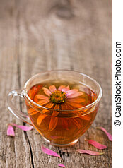 Cup of echinacea tea on old wooden table with copy space for your text