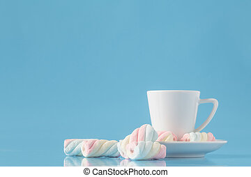 Cup of espresso coffee and twisted american marshmallow on blue
