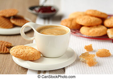 Cup of espresso with coconut cookies on a plate