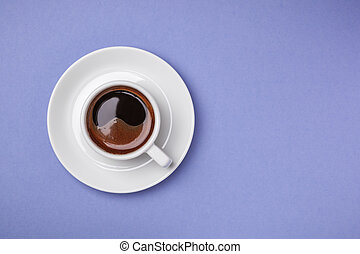 Cup of espresso with saucer on blue background.