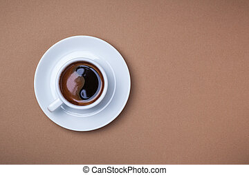 Cup of espresso with saucer on brown background.