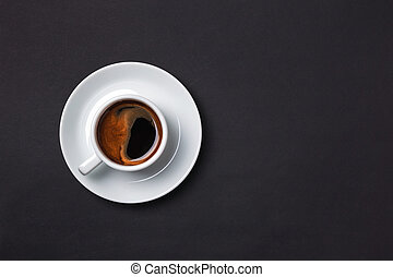 Cup of espresso with sauser on black background.
