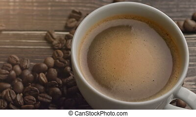 cup of fresh espresso on wooden table with beans