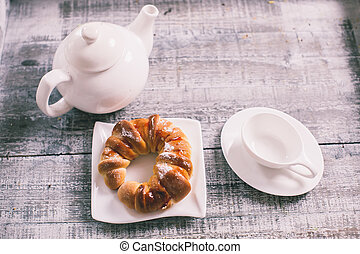 Cup of fruit tea with croissant