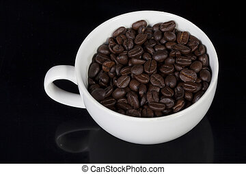 Cup of full roast coffee beans