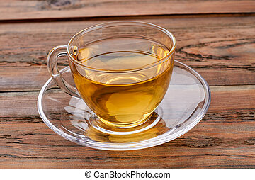 Cup of green tea on brown wooden background.