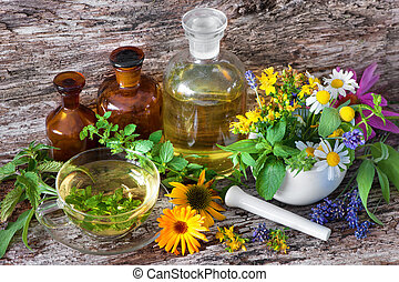 Cup of herbal tea with medicinal bottles and healing herbs in mortar