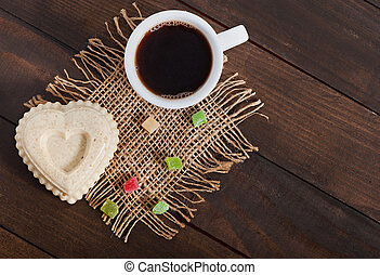 Cup of hot aromat coffee and a sesame dessert in the shape ...