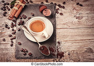 Cup of hot black coffee in setting with roasted coffee...