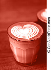 Cup of hot cappucino on wooden table with heart art latte.