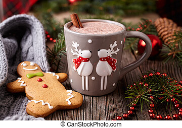 Cup of hot chocolate or cocoa drink with two cute deer, cinnamon and gingerbread man christmas cookies in new year tree decorations frame on vintage wooden table background. Homemade traditional celebration dessert recipe.