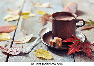 Cup of hot chocolate with brown sugar on wooden background